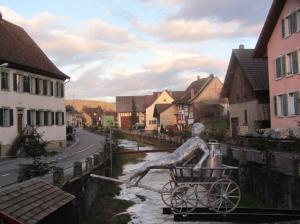 Hans Russenberger's latest public sculpture, 'de Laaterwägelibueb' spans the village creek. Russenberger was one of 30 artists to display at Scheitheim's art show.