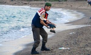 Rescue worker brings drowned refugee boy to shore